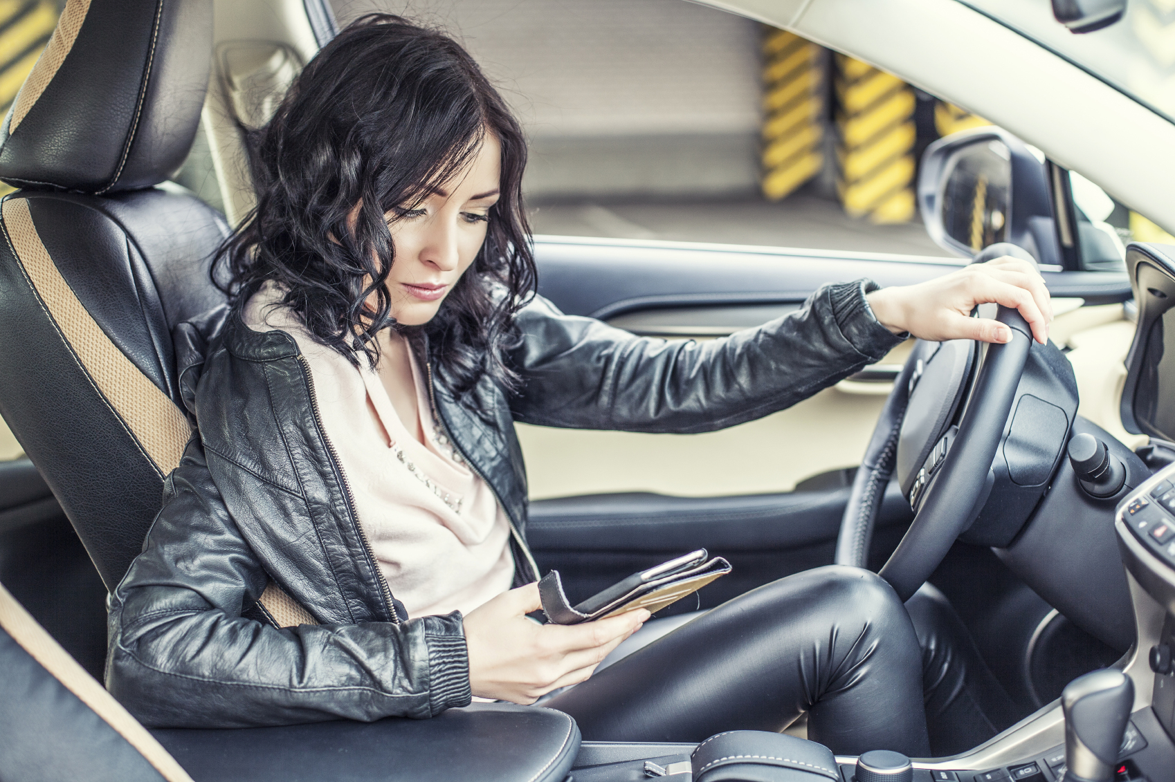 Beautiful female model in leather clothes with a white car and a smartphone in the Parking lot