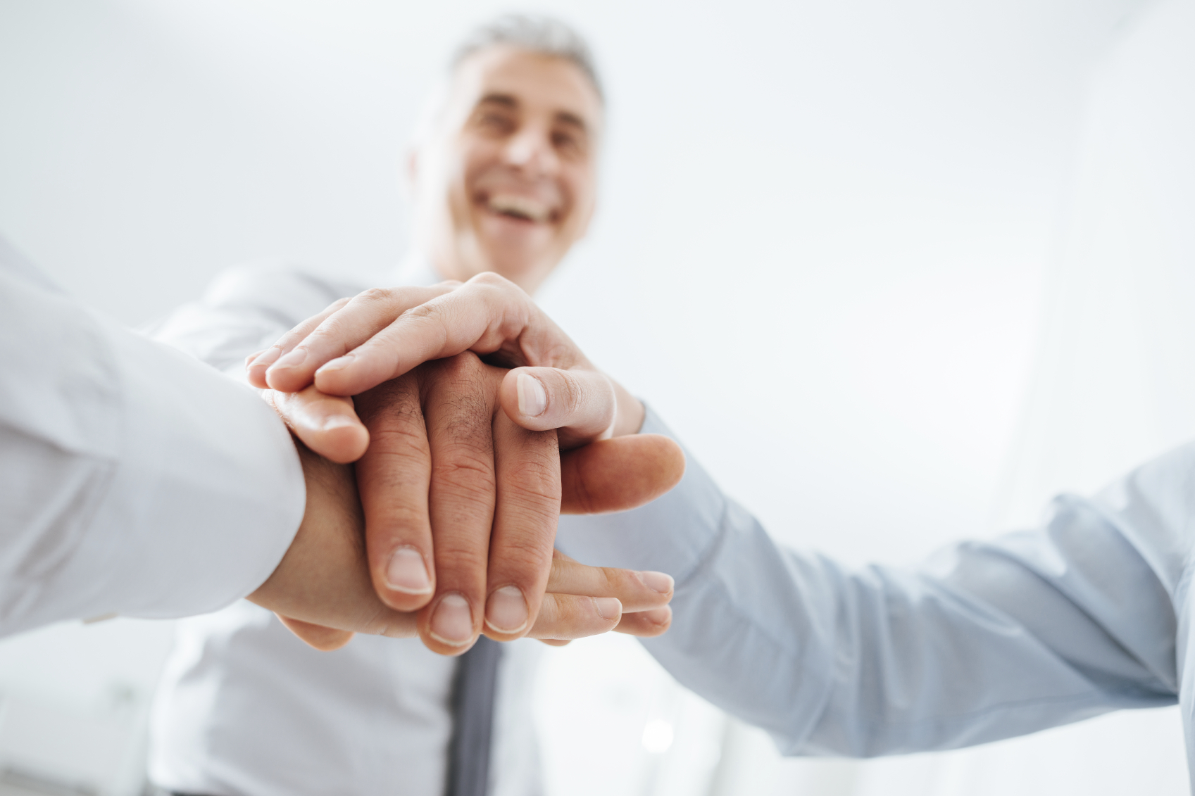 Cheerful business team stacking hands and smiling, teamwork and success concept, hands close up